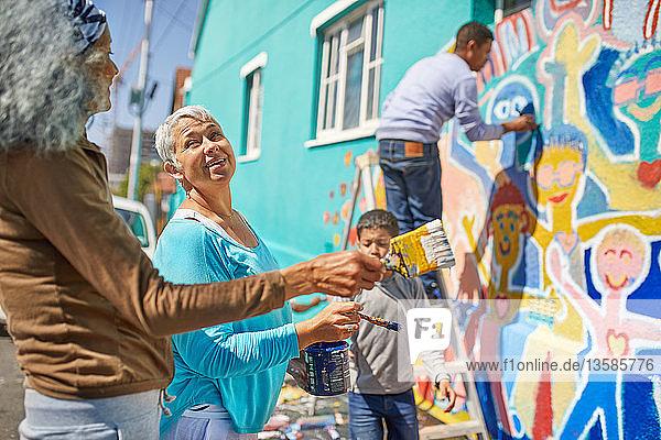 Community volunteers painting vibrant mural on sunny urban wall