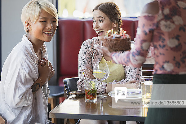 Excited young women friends celebrating birthday with cake in restaurant