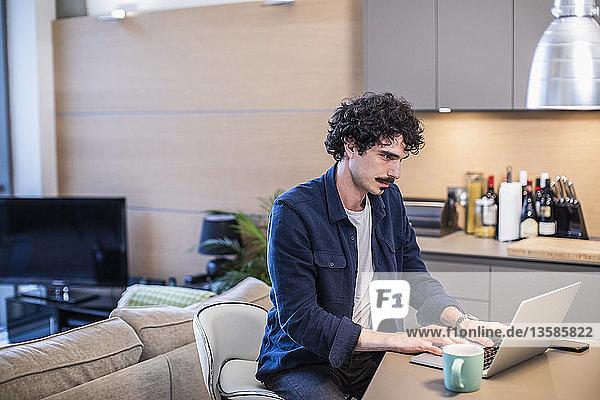 Man working at laptop in apartment kitchen