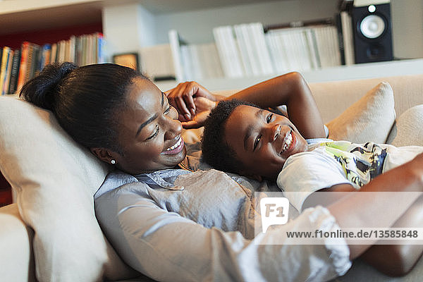Portrait happy  affectionate mother and son cuddling on living room sofa