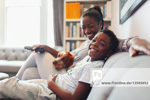 Portrait happy mother and son with dog watching TV on living room sofa