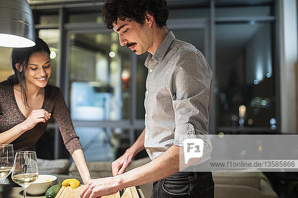 Couple cooking dinner in apartment kitchen at night