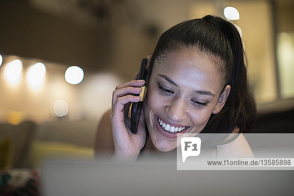 Happy woman talking on smart phone at laptop