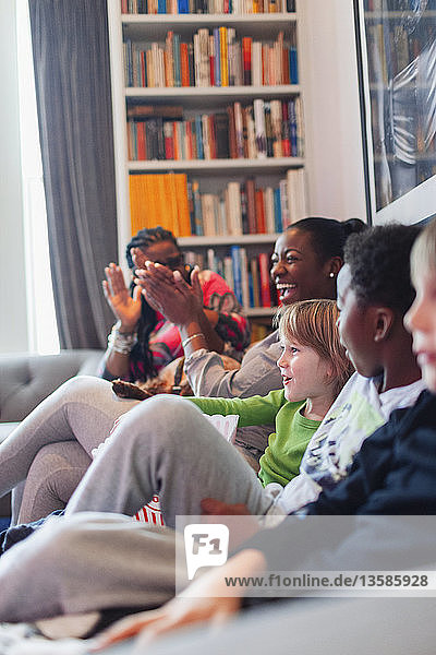 Happy family clapping on living room sofa
