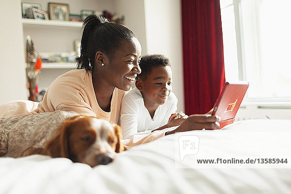 Mother and son using digital tablet on bed next to sleeping dog