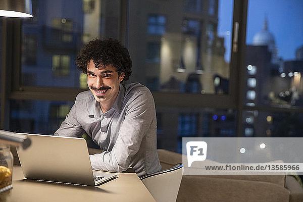 Portrait smiling man using laptop in urban apartment at night