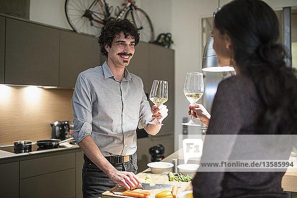 Couple preparing dinner and drinking white wine in apartment kitchen