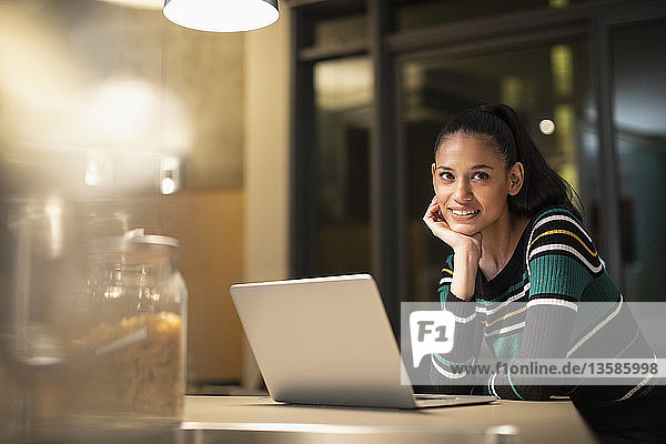 Portrait smiling  confident woman using laptop at home at night