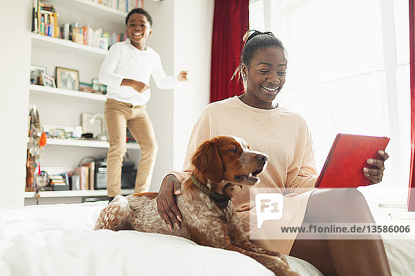 Boy jumping on bed behind dog and mother with digital tablet