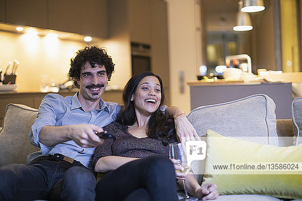 Happy couple watching TV and drinking white wine on living room sofa