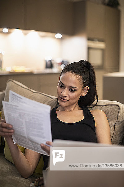Woman reading paperwork at laptop on sofa