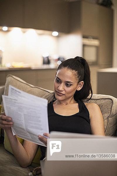 Woman reading paperwork at laptop on sofa