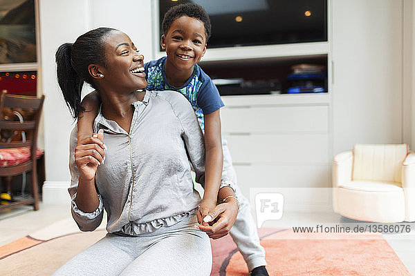 Portrait playful  happy mother and son in living room