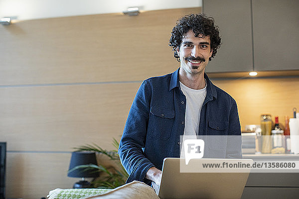 Portrait smiling man using laptop in apartment kitchen