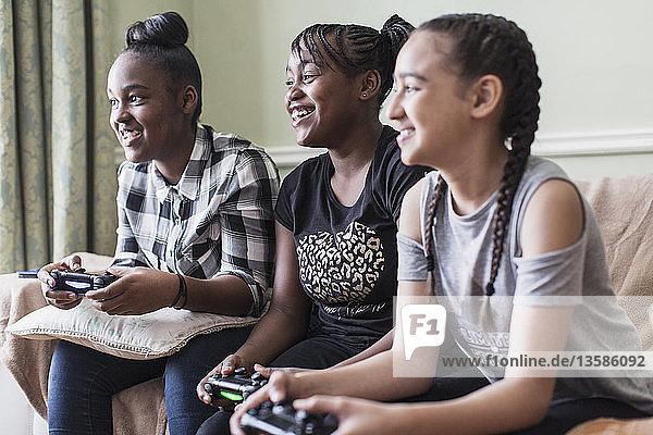 Tween girl friends playing video game in living room