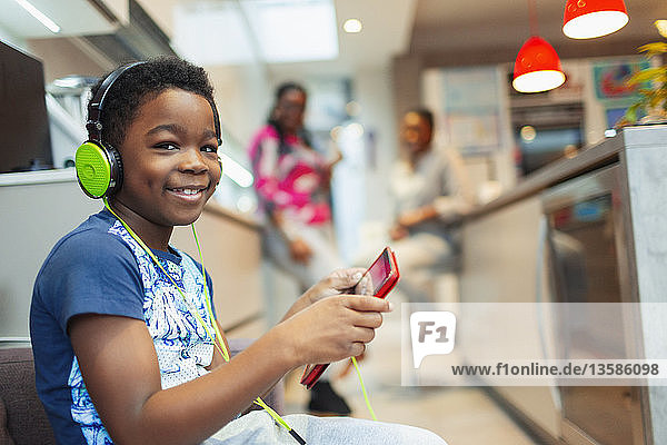 Portrait smiling  confident boy playing video game with headphones and digital tablet
