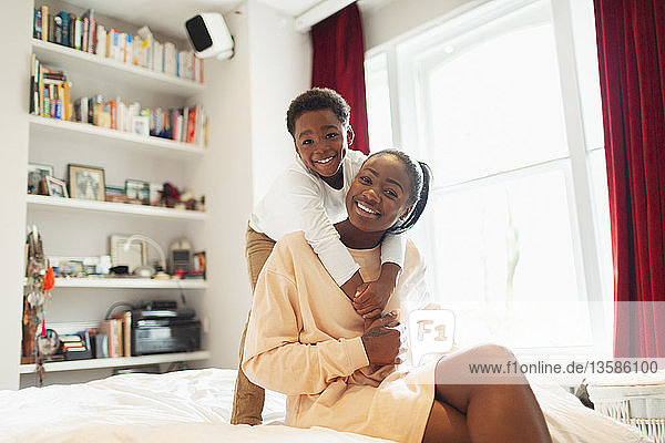 Portrait affectionate mother and son hugging on bed