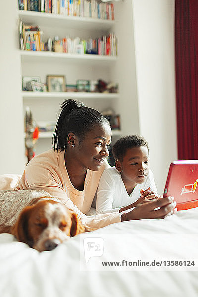 Dog sleeping next to mother and son using digital tablet