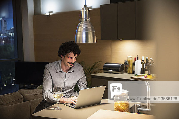 Man drinking white wine at laptop in apartment kitchen at night