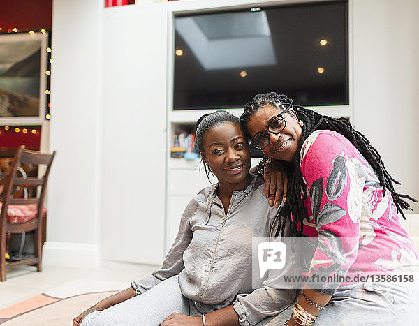 Portrait happy mother and adult daughter in living room