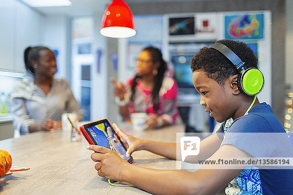 Boy with headphones and digital tablet playing video game