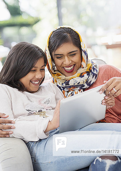 Laughing  happy mother in hijab and daughter using digital tablet