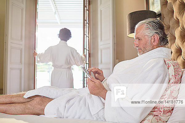 Mature man in spa bathrobe using digital tablet on hotel bed