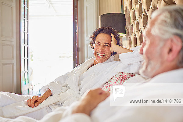 Happy  laughing mature couple relaxing on hotel bed