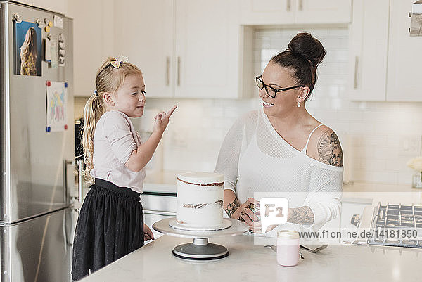 Mother and daughter decorating cake in kitchen