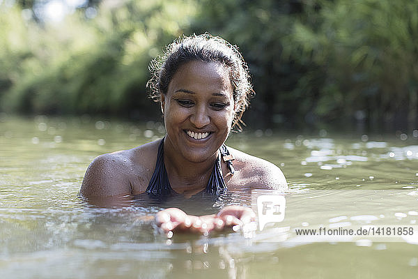 Happy woman swimming in river