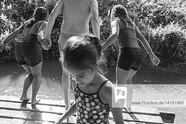 Family playing  jumping into sunny river