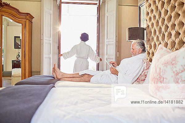 Mature couple in bathrobes relaxing in hotel bedroom