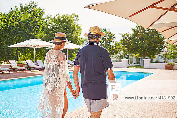 Mature couple holding hands  walking along sunny resort swimming pool