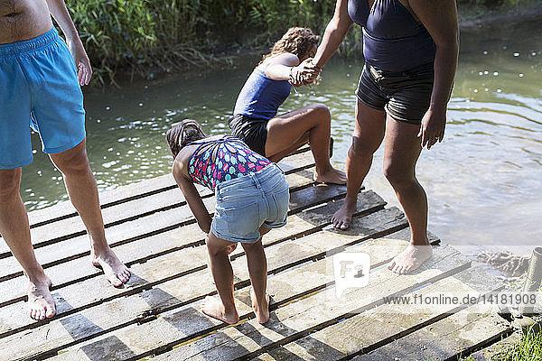 Family swimming  playing on riverside dock