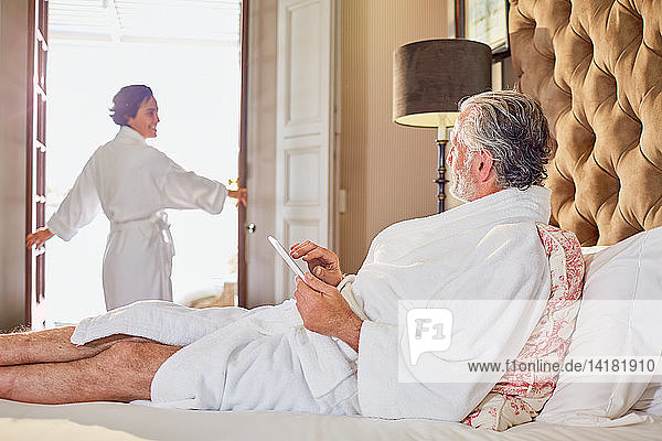 Mature couple in bathrobes relaxing in hotel room