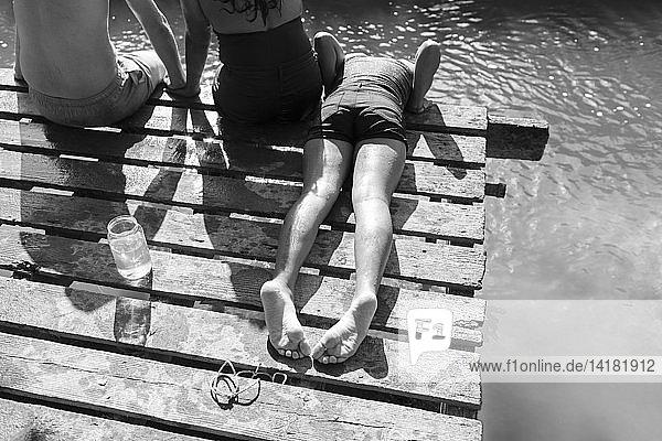 Family relaxing on dock at sunny riverside