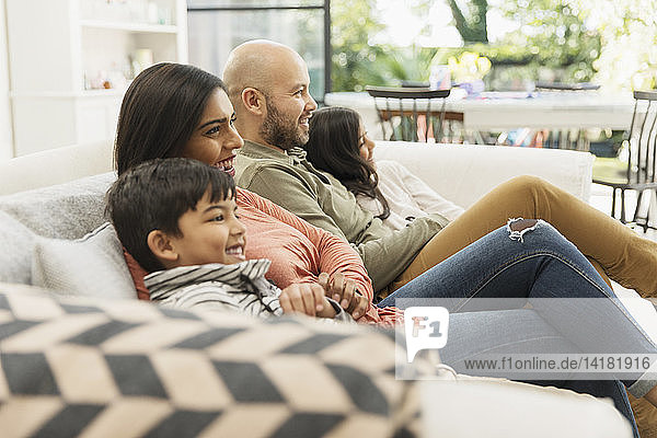 Family watching TV on living room sofa