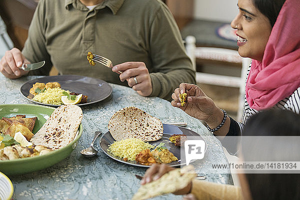 Woman in hijab eating dinner with family at table