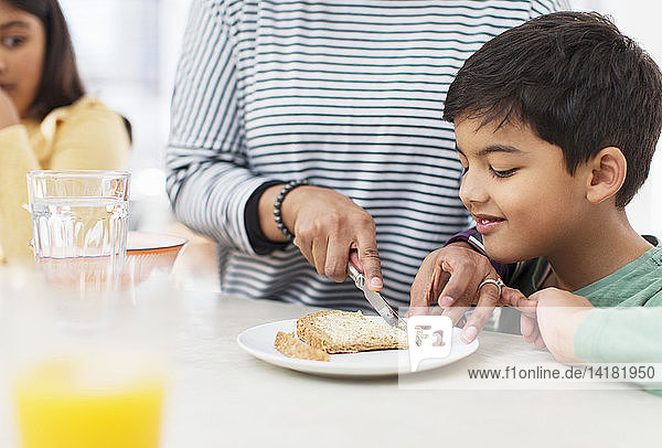 Mother cutting crusts off bread for son