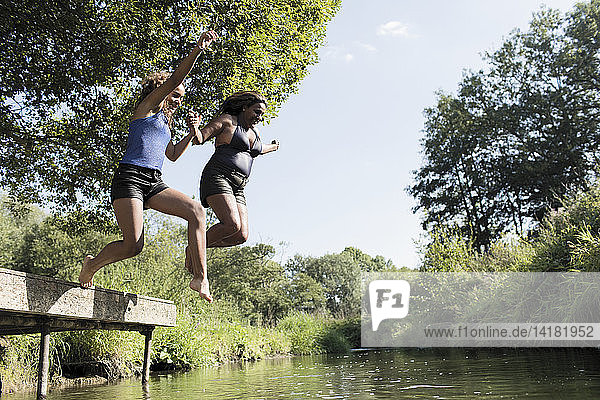 Carefree mother and daughter jumping into river