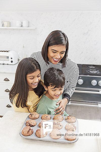 Mother and children baking chocolate muffins in kitchen