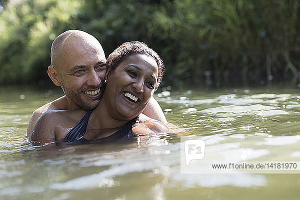 Happy  affectionate couple in sunny river
