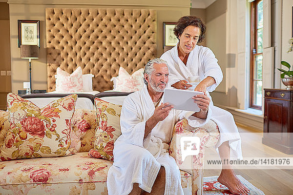 Mature couple in spa bathrobes using digital tablet in hotel room