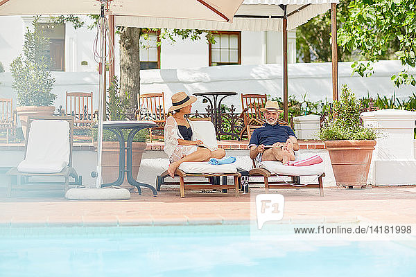 Mature couple relaxing on lounge chairs at resort poolside