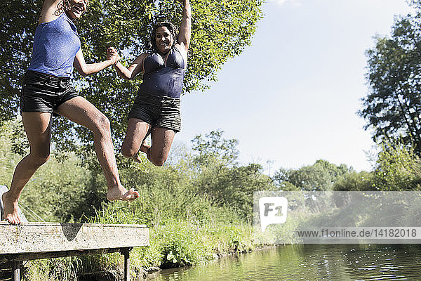 Playful mother and daughter jumping into sunny river
