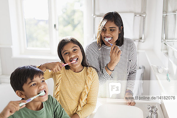 Portrait happy family brushing teeth in bathroom