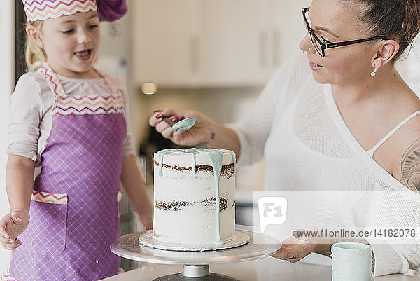 Mother and daughter decorating cake