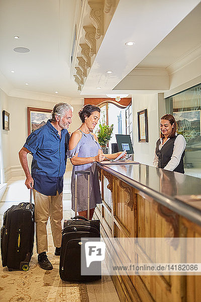 Mature couple with suitcases checking in at hotel reception