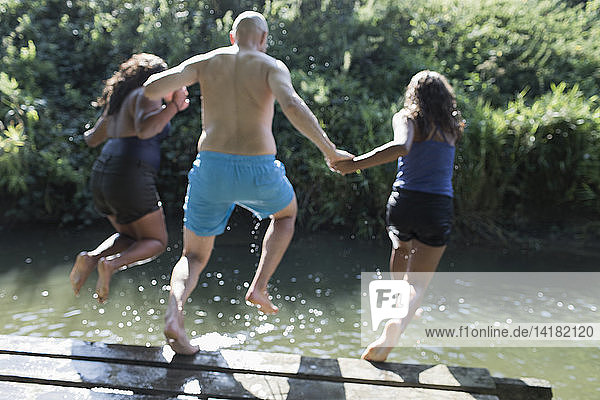 Playful family jumping into sunny river