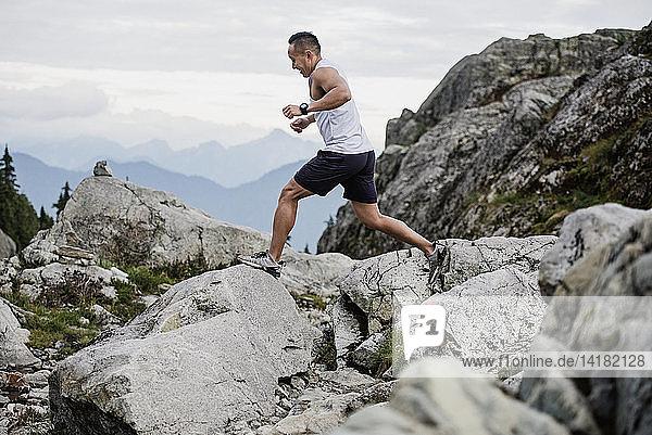 Man hiking  jumping across rocks  Dog Mountain  BC  Canada